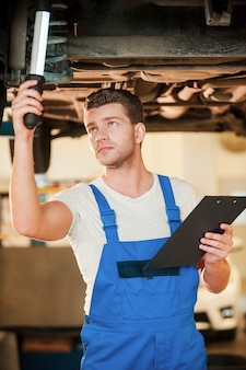 Checking everything for defects. confident young man in uniform holding lamp while standing underneath a car in workshop