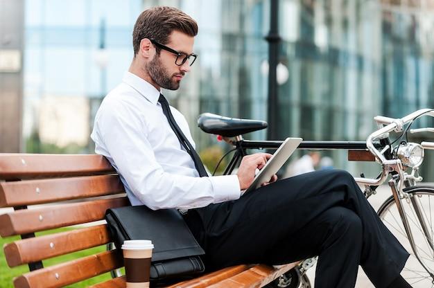 彼のビジネススケジュールをチェックしています。バックグラウンドでオフィスビルと彼の自転車の近くのベンチに座ってデジタルタブレットに取り組んでいる自信を持って青年実業家の側面図