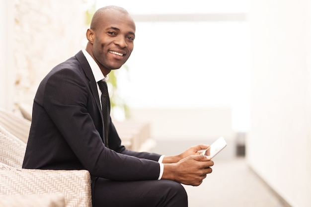 이동 중에 그의 일정을 확인합니다. 디지털 태블릿에서 작업하고 카메라를 보며 웃고 있는 쾌활한 젊은 아프리카 사업가의 측면
