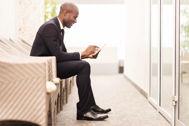 이동 중에 그의 일정을 확인합니다. 의자에 앉아 디지털 태블릿 작업을 하는 쾌활한 젊은 아프리카 사업가의 측면