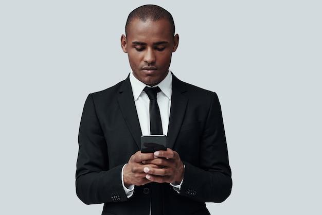 수입 메시지를 확인합니다. 회색 배경에 서 있는 동안 스마트 폰을 사용하여 정장을 입은 매력적인 젊은 아프리카 남자