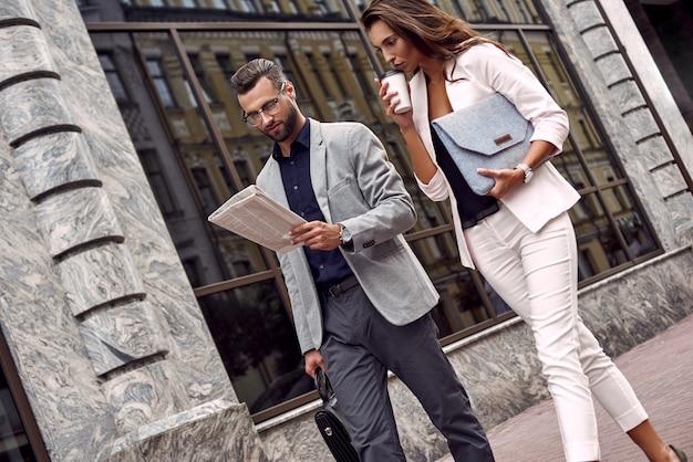 최신 뉴스를 확인하는 두 젊은 사업가가 독서를 하는 도시 거리에서 밖에 걸어가고 있습니다.