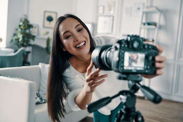 メディア機器の確認。彼女のブログのために新しいビデオを作っている間、ビデオカメラを調整して、微笑んでいる魅力的な若い女性
