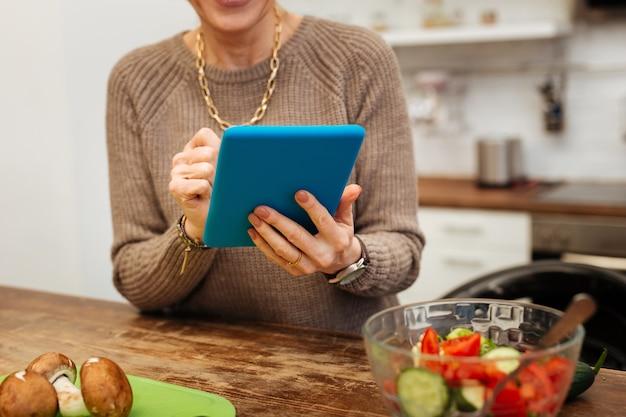メディアをチェックしています。青いタブレットを運び、それに入力するベージュの暖かいセーターの成熟した女性