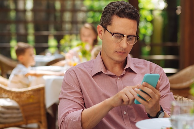 メッセージを確認しています。夏のテラスに座って昼食をとりながら彼のメッセージをチェック忙しいビジネスマン