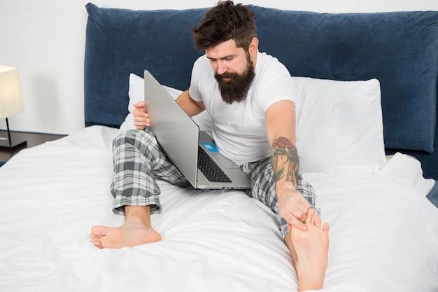 メッセージを確認しています。ベッドの上のパジャマでひげを生やした成熟した男性。眠って起きている。エネルギーと倦怠感。コンピューターを持つビジネスマン。ひげを生やした男のヒップスターはラップトップで動作します。寝室の残忍な眠そうな男。
