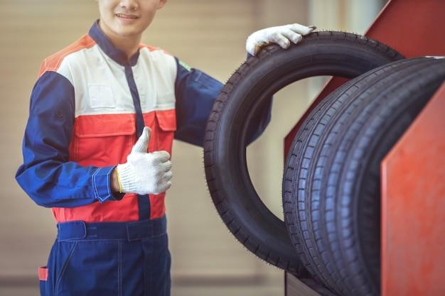 自動車修理サービスセンターの大きな倉庫で新しい標準タイヤをチェックする