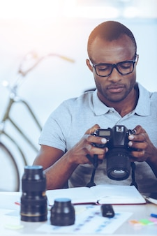 Checking photos. confident young african man in casual checking photos at his camera while sitting at his working place