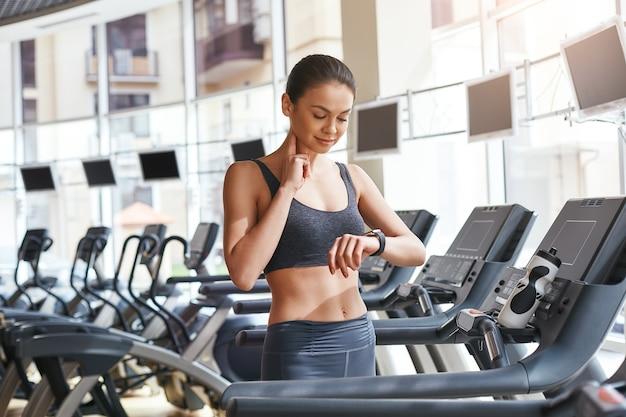 달리기 후 심장 박동수를 측정하는 운동복을 입은 젊고 아름다운 여성의 맥박 확인