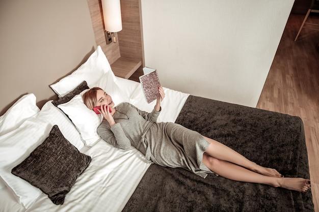 スケジュールを確認しています。高級ホテルで休んでベッドに横たわっている間彼女のスケジュールをチェックする実業家