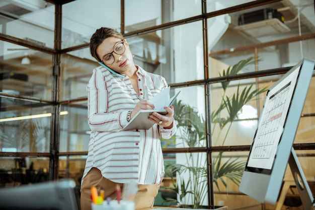 スケジュール確認中。忙しい妊娠中のビジネスマンが、会議の準備をしながらスケジュールをチェック