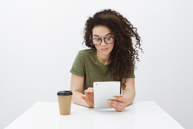 Проверка расписания в ожидании клиента. портрет красивой уверенной в себе женской творческой коллеги в очках, сидящей за столом