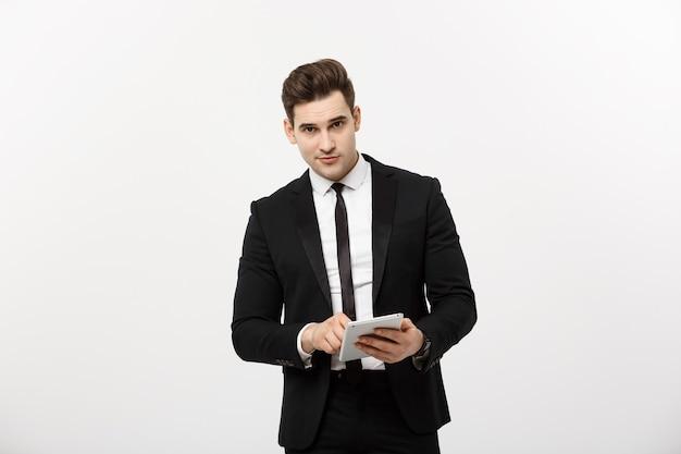 統計を確認しています。成功した自信のあるビジネスマンは立って、ビジネスセンター内のタブレットでオンラインニュースをチェックします。フォーマルなスーツを着た若いビジネス。