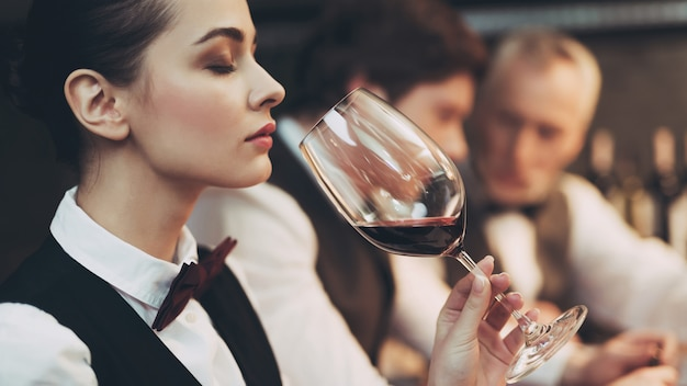 Checking taste, color, sediments of wine.