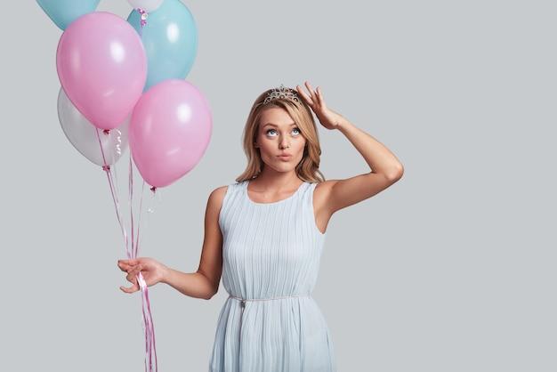 크라운을 확인 중입니다. 회색 배경에 서서 풍선을 들고 손으로 머리를 만지는 매력적인 젊은 여성