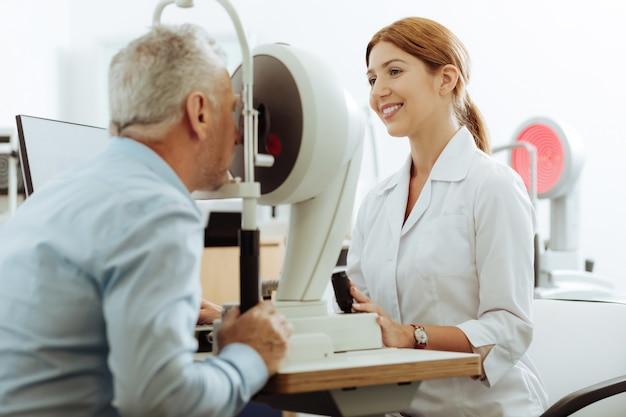 視力をチェックします。仕事中に微笑んでいる魅力的な資格のある赤毛の眼科医