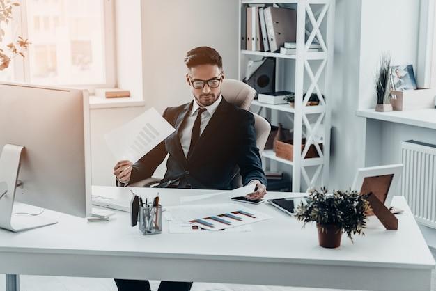 Проверка отчетов. красивый молодой человек в полном костюме, работающий с документами