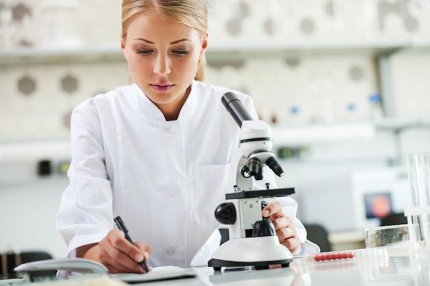 결과를 확인 중입니다. 그녀의 작업장에 앉아 있는 동안 현미경을 사용하고 메모장에 글을 쓰는 진지한 젊은 여성 과학자
