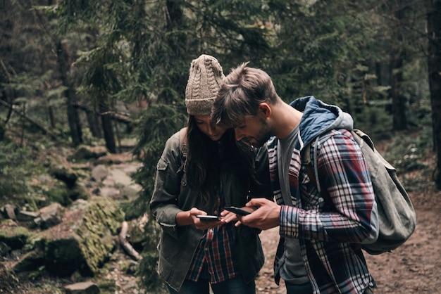 Проверка маршрута. красивая молодая пара с помощью своих смартфонов во время прогулки вместе в лесу