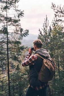 ルートを確認しています。森の中に立っている間双眼鏡を通して目をそらしているバックパックを持つ現代の若い男