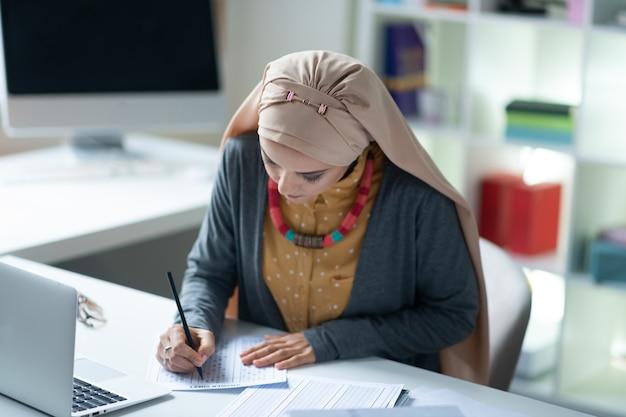 テストをチェックします。テーブルに座って生徒のテストをチェックする素敵なネックレスを身に着けているイスラム教徒の教師