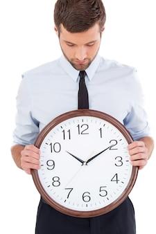 時間を確認します。シャツとネクタイのハンサムな若い男は、彼の手で時計を保持し、白い背景で隔離に立っている間それを見て