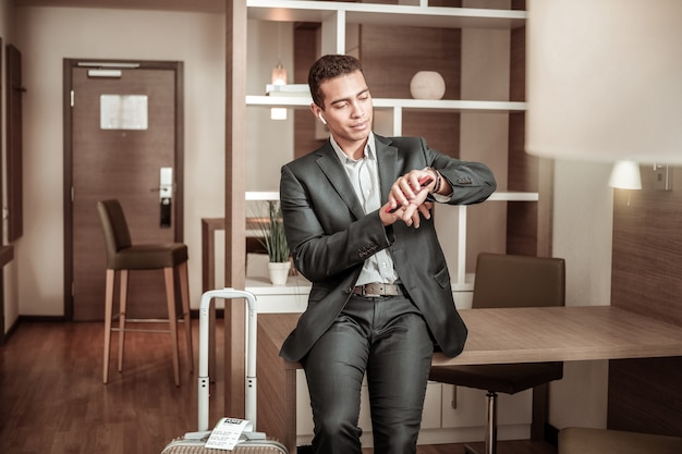 時間を確認しています。ビジネス会議に遅れて走っている間、彼の時計で時間をチェックする黒髪のビジネスマン