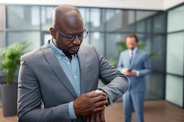 Проверяем время. темнокожие бородатые бизнесмены проверяют время, опаздывая на встречу