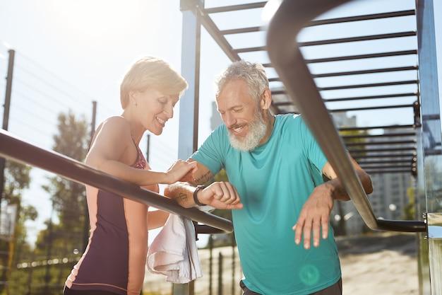 Проверка результатов тренировок счастливая зрелая семейная пара в спортивной одежде, глядя на умные часы и