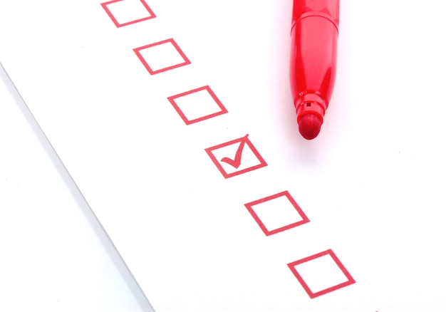 Контрольный список и красный маркер крупным планом