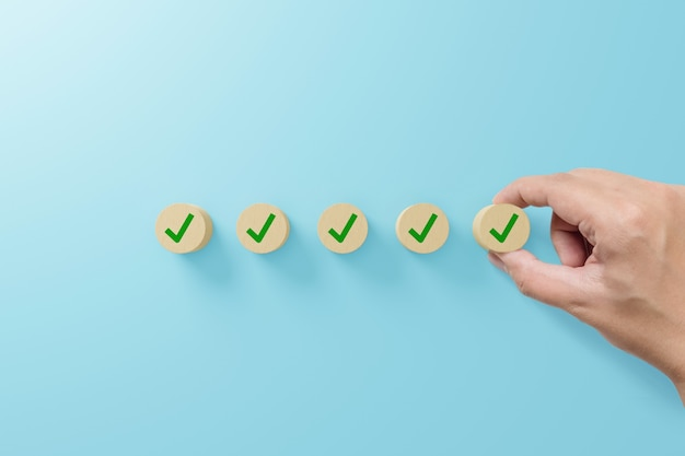 Checklist and check mark concept. check mark on wooden blocks on light blue background
