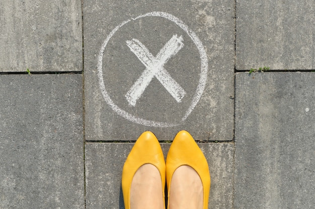 Checkmark no sign on gray sidewalk with woman legs, top view