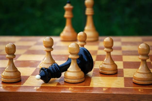 チェックメイティング-黒いチェスの女王が倒れ、チェス盤の白いポーンに囲まれました