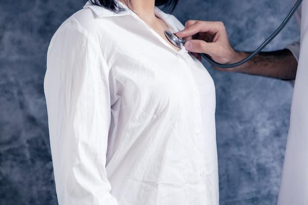 청진기로 여성의 심장을 확인합니다.