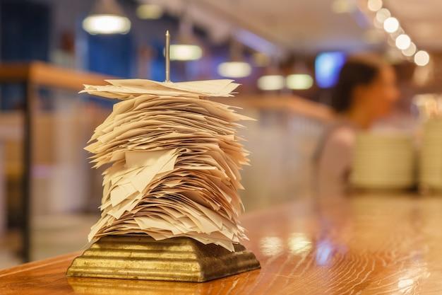 Чеки по выполненным заказам в баре или на кухне ресторана насаживают на острую тонкую железную иглу на подставке. концепция проверки, стенд для проверки, флажок