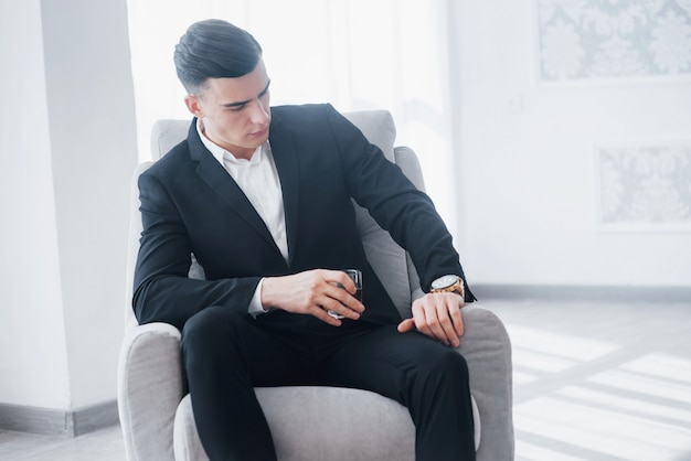 명품 시계의 시간을 확인합니다. 흰색의 자에 앉아 검은 양복에 젊은 우아한 남자와 알코올 유리를 보유하고 있습니다.