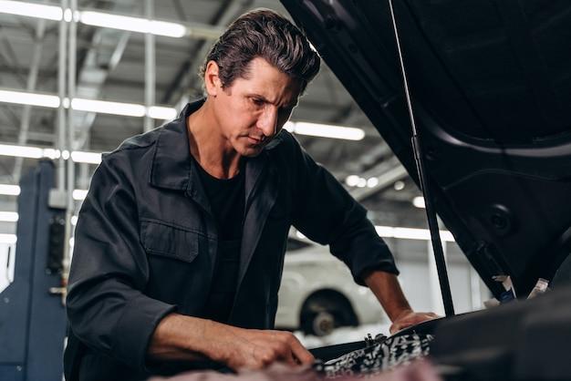 건강 진단. 서비스에서 차에서 일하는 동안 차안을 바라보는 제복을 입은 미남 정비사의 허리 초상화. 스톡 사진