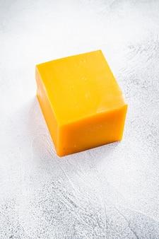 台所のテーブルの上のチェダーチーズブロック。白色の背景。上面図。