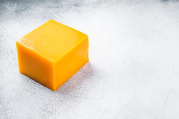 台所のテーブルの上のチェダーチーズブロック。白いテーブル。上面図。
