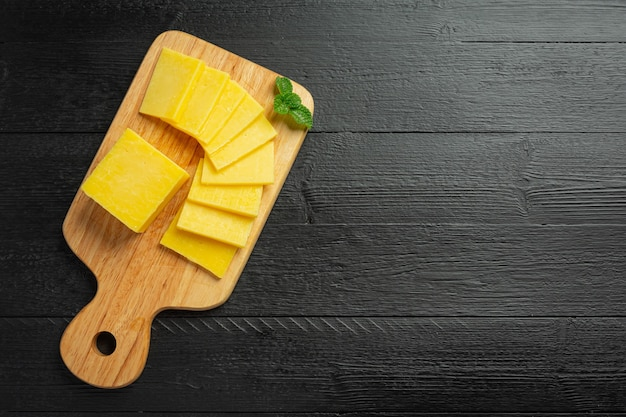 Cheddar cheese on dark wooden surface