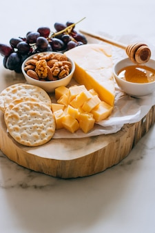 Cheddar cheese, grapes, nuts, honey and cracker in wooden board on marble