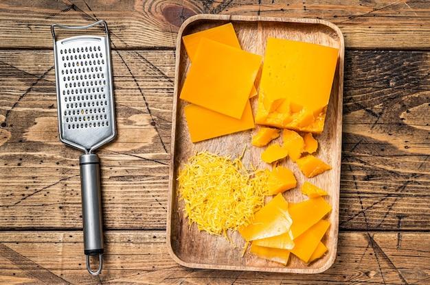 チェダーチーズおろしと木製トレイにさいの目に切った。木製の背景。上面図。