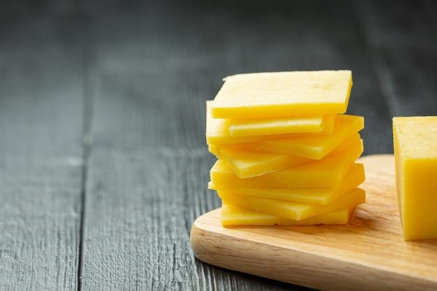 暗い木の表面のチェダーチーズ 無料写真