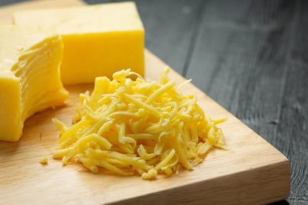 暗い木の表面のチェダーチーズ