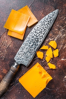 チェダーチーズをキッチンのテーブルでナイフでスライスしました。暗い背景。上面図。