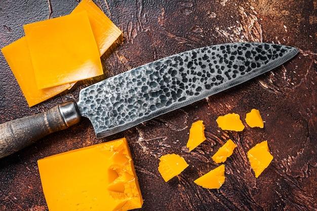チェダーチーズをキッチンのテーブルでナイフでスライスしました。暗いテーブル。上面図。
