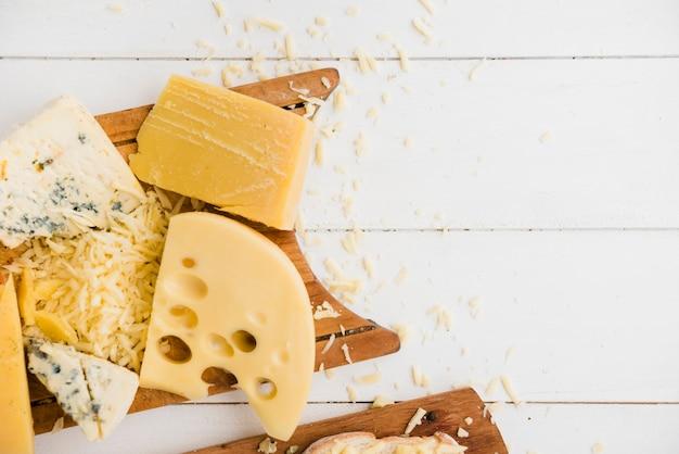 Чеддер; маасдам и голубой сыр на разделочной доске над столом