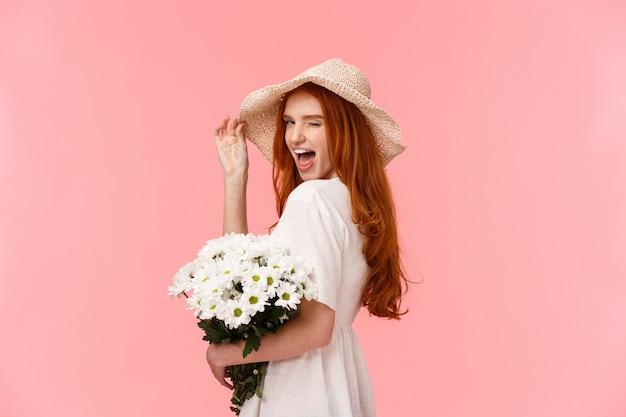 生意気で自信を持って見栄えの良い、魅力的な赤毛の女性白いドレス、麦わら帽子