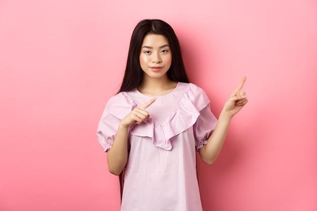 Нахальная азиатская девушка показывает интересную рекламу, указывая пальцами прямо на логотип и хитро улыбается, намекая на выгодную сделку, розовый фон.