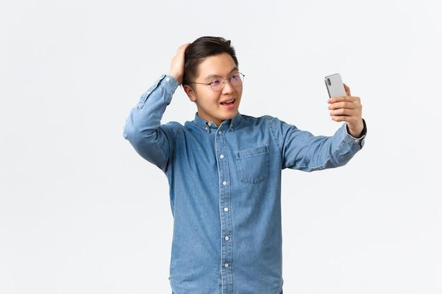 Sfacciato uomo asiatico fiducioso con gli occhiali e l'apparecchio che si sente impertinente, scatta selfie, si spazzola i capelli con la mano, posa per una foto, usa l'app filtro sul cellulare, il blogger fa post su internet.